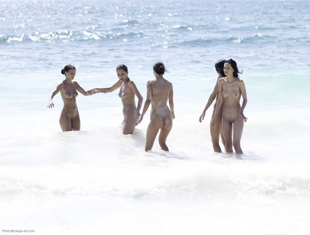 Nudist girls splashing around and playing in shallow water